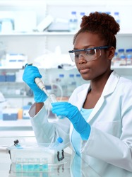 African-american scientist or graduate student in lab coat and protective wear works in modernl laboratory