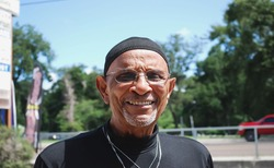 African American Senior Man with glasses on, a black skull cap, silver jewlery.  Outside on a beautiful day the sun is shining.