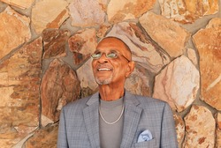 African American Senior Man with glasses on, a gray shirt and blue gray plaid suit  with a blue scarf and silver jewlery.  The gentleman is looking upward against a brick wall.
