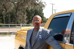 African American Senior Man with glasses on, a gray shirt and blue gray plaid suit  with a blue scarf and silver jewlery.  The gentleman is standing next to a yellow truck outside on a beautiful day.