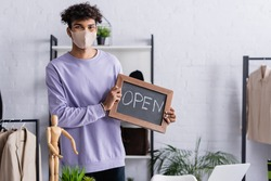 African american showroom proprietor in protective mask holding chalkboard with open lettering near clothes