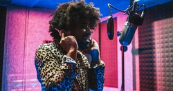 African american singer recording new music album inside boutique studio - Main focus on silver microphone