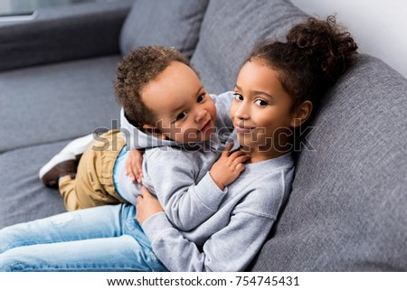 african american sister sitting on sofa with her little brother at home #754745431