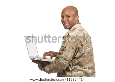 African American soldier looks over his shoulder while typing on a computer