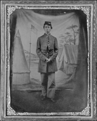 African American soldier posed in front of quaint studio backdrop of tents in a military camp with a prominent U.S. flag. The soldier is standing on the dirt ground, by a traveling photographer. 1865.