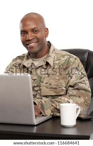 African American soldier smiles while working on a computer