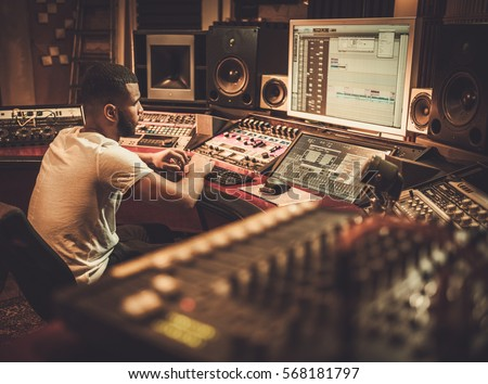 African american sound engineer working at mixing panel in boutique recording studio. #568181797
