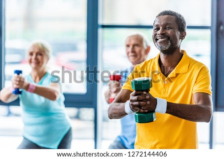 african american sportsman and his friends exercising with dumbbells at gym