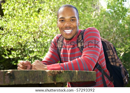 African American student wearing backpack sitting at outdoor table