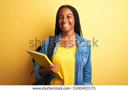 African american student woman wearing backpack and book over isolated yellow background with a happy face standing and smiling with a confident smile showing teeth