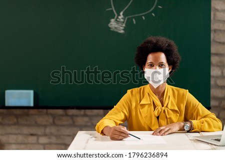 African American teacher with protective face mask holding a class at the school. Copy space.