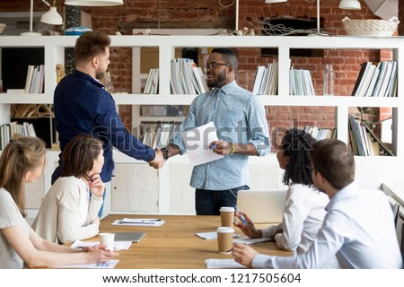 African American team leader or boss handshake Caucasian employee congratulating with work success, black manager shake hand of male worker greeting with high results and personal achievements #1217505604