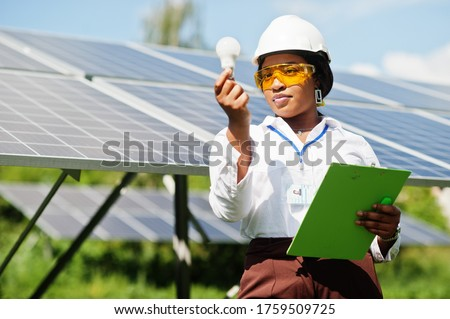 African american technician check the maintenance of the solar panels. Black woman engineer at solar station.