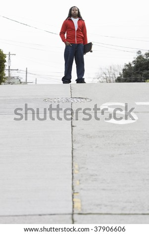 African American Teen Boy Holding Skateboard at Top of Street