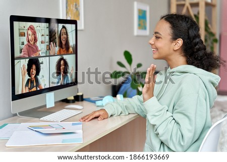 African american teen girl talking to happy multicultural diverse teenage friends during online virtual chat video call in group conference social distance chat virtual meeting using computer at home.