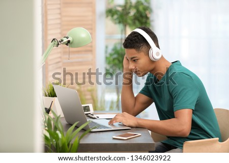 African-American teenage boy with headphones using laptop at table in room