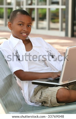 African American Teenager Boy on Laptop Computer Outdoors on a bench, city street, urban setting