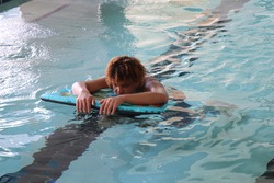 African American teenager  having fun laying on a body board at an indoor pool