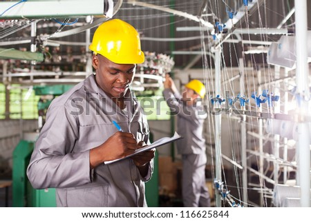 african american textile worker writing report