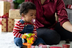 African American toddler little boy crying on Christmas at home. toddler little boy crying near his mother on Christmas. Christmas holiday celebration, Merry Christmas and Happy Holidays