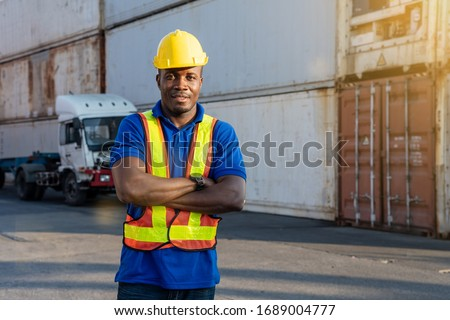 African American transportation factory truck driver with yellow helmet and safety vest is standing and smiling by action arms crossed in front of lorry at container yard of port on evening.