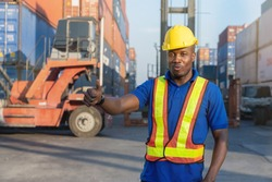 African-American truck driver with safety equipment, safety vest and yellow helmet is standing in front of big forklift and truck at container yard. He is enjoy working and show thumbs up sign.