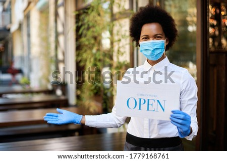 African American waitress holding open sign while reopening sidewalk cafe after COVID-19 pandemic.
