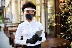 African American waitress wearing protective face mask and visor while holding touchpad and reopening sidewalk cafe during COVID-19 epidemic.