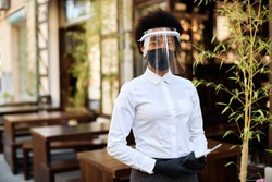 African American waitress wearing protective face mask and visor while standing at outdoor cafe and looking at camera.