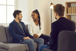 African american wife begging asking for forgiveness caucasian husband at specialist consultation in home office. Psychoanalyst or family psychotherapist, financial advisor or lawyer appointment