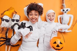 African American woman and small child wear halloween costumes hold spider and carved pumpkin jack o lantern pose against orange background with spooky handmade toys around. Happy celebration