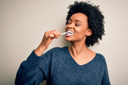 African american woman brushing her teeth using tooth brush and oral paste, cleaning teeth and tongue as healthy health care morning routine