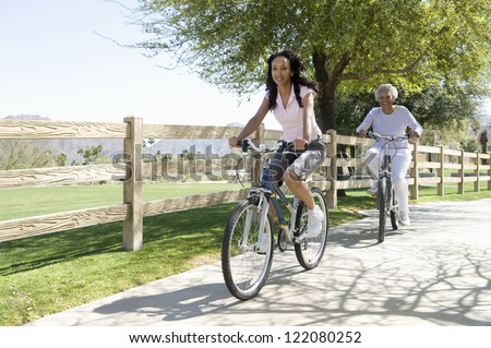 African American woman cycling with her mother in park by wooden fence