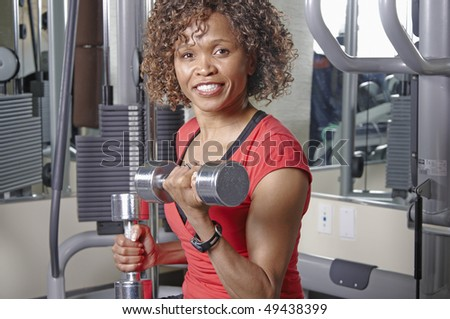 African American woman doing bicep curls in a gym