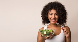 African-american woman eating vegetable salad over light background with copy space