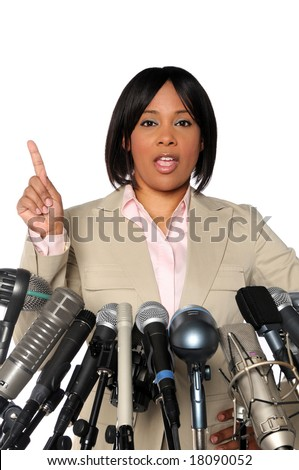 African American woman giving speech behind microphones during press conference