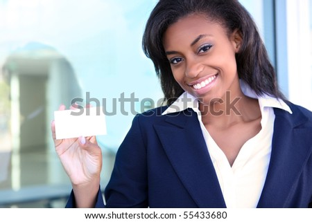 African American woman holding business card at office building