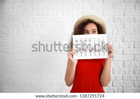 African-American woman holding calendar with marked days of menstruation on white background