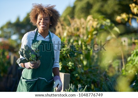 african american woman holding freshly picked kale from comnunal community garden posing for portrait #1048776749
