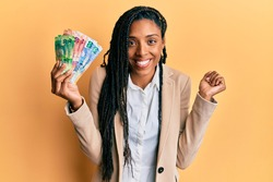 African american woman holding south african rand banknotes screaming proud, celebrating victory and success very excited with raised arm