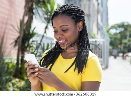 African american woman in a yellow shirt texting message with mobile phone