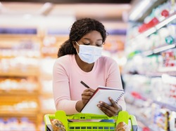 African American woman in face mask doing shopping at supermarket, adding products to grocery list, writing in notebook. Black female customer purchasing goods at big mall