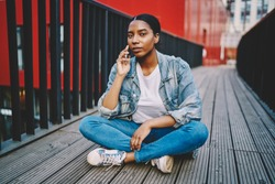 African American woman in jeans jacket looking at camera while talking on mobile phone in roaming, portrait of serious dark skinned hipster girl making cellphone call resting outdoors in urban setting