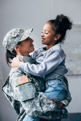 african american woman in military uniform holding daughter on arms at home