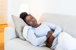African American Woman in painful expression holding hands against belly suffering menstrual period pain, lying sad on home bed, having tummy cramp in female health concept