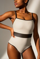 African American woman in white one-piece swimsuit with black stripe beach fashion