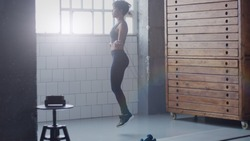 african american woman makes a jump rope routine in sunny loft for healthy life full body side view