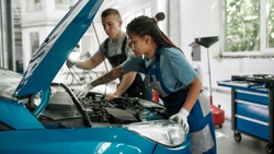 African american woman, professional female mechanic repairing car engine, tighten, screw with spanner while her colleague holding torch under car hood at service station. Side view. Web Banner