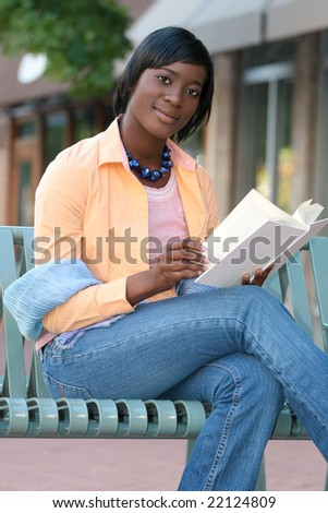 African American Woman reading a book on a bench outdoors in a city setting