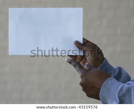 African-American woman's hands holding and pointing to blank space for add